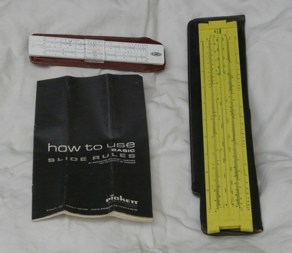 Two slide rules and an instruction manual.